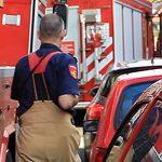 Brandweerman loopt tussen brandweervoertuigen en auto's door
