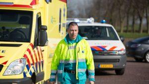 Ambulancemedewerker loopt langs ambulance met politieauto op achtergrond