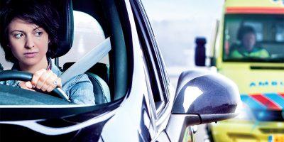 Vrouw kijkt in zijspiegel naar naderende ambulance