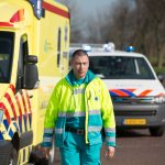 Ambulancemedewerker naast ambulance en voor politieauto