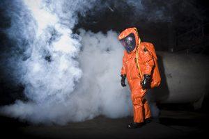 Brandweerman in oranje beschermingspak tegen gevaarlijke stoffen