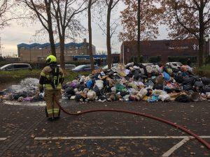 Brandweerman blust afval na containerbrand