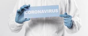 Zorgmedewerker houdt bord vast met de tekst coronavirus