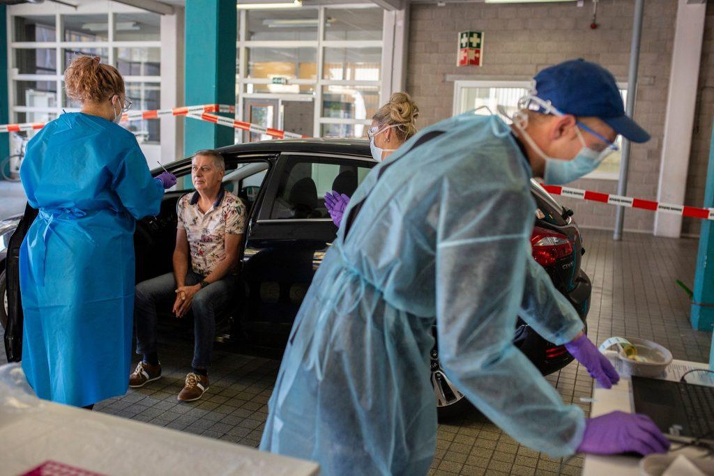 Man ondergaat coronatest in teststraat waar 3 GGD-medewerkers aanwezig zijn