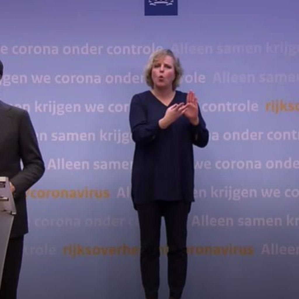 Een gebarentolk beeld de woorden van Mark Rutte en Hugo de Jonge uit tijdens een persconferentie