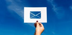 Vrouwenhand houdt papiertje met e-mail icoon in de lucht