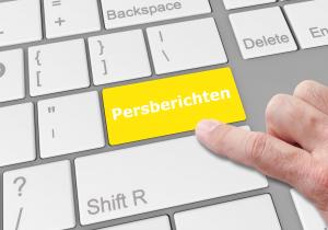 Vinger klikt op de 'enter knop' op toetsenbord met de tekst persberichten