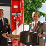 Burgemeester en brandweerman bij tankautospuit