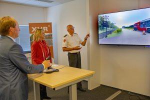 Burgemeesters kijken naar presentatie op scherm